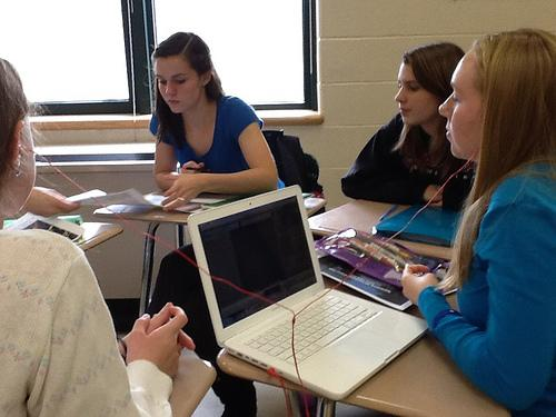 Working hard, students Leah Raczynski (far left), Samantha Lee, Sarah Randall, and Emily Day (far right) organize and prepare for the upcoming political debate.  Photo by Sydney Lauro