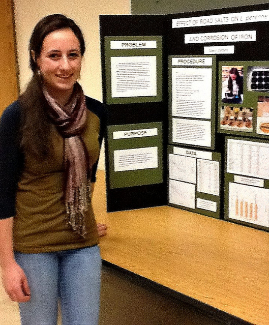 "Alexis Stefano stands in front of her 1st prize science fair project entitled ""The Effects of Road Salts on L. Perenne and Corrosion of Iron."" Photo by Blair Guild"