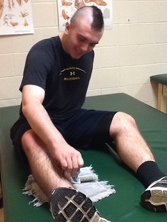 Senior lineman Connor Sullivan ices his ankle in preparation for practice. Photo by Lexie Papadellis