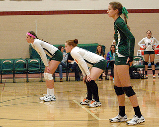 In a previous game against Medfield, Senior Volleyball Captains, (left to right) Tess Chandler, Lindsay Manning, and Kristen Cooprider, anticipate the next play  on October 12th, 2012. Photo by Elizabeth Clark