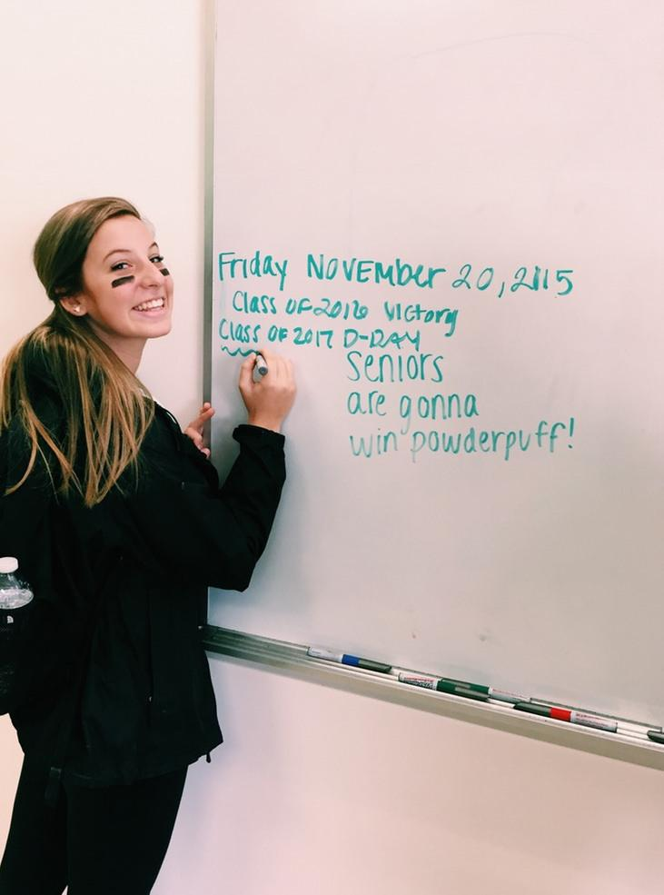 Senior Emily Sheridan writes a message for the juniors on the whiteboard in the girls team room. Photo by Alli McNulty.
