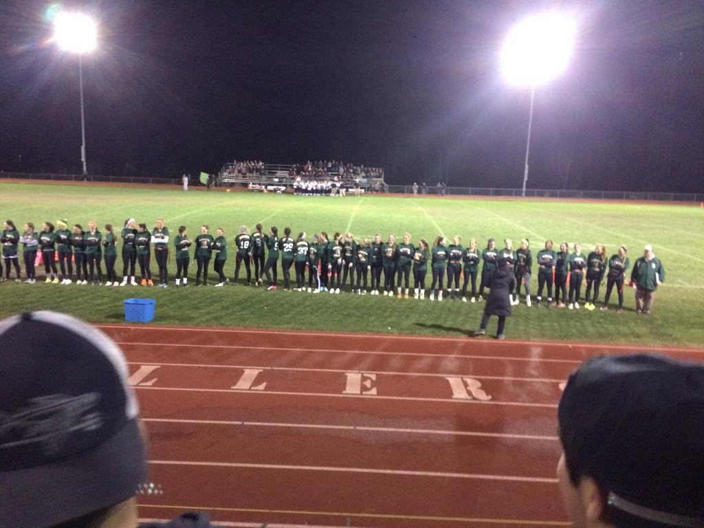 The Hopkinton High School senior powderpuff team prepares for the big game as they listen to the National Anthem. Photo by Alli McNulty.