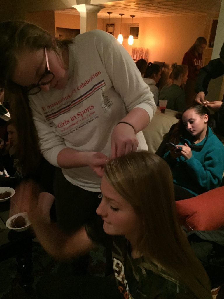 The night before the big game, senior Brigid Marquedant (standing) cornrows the hair of the senior girls, starting with Emily Hoffman (sitting). Photo by Emma Zack.