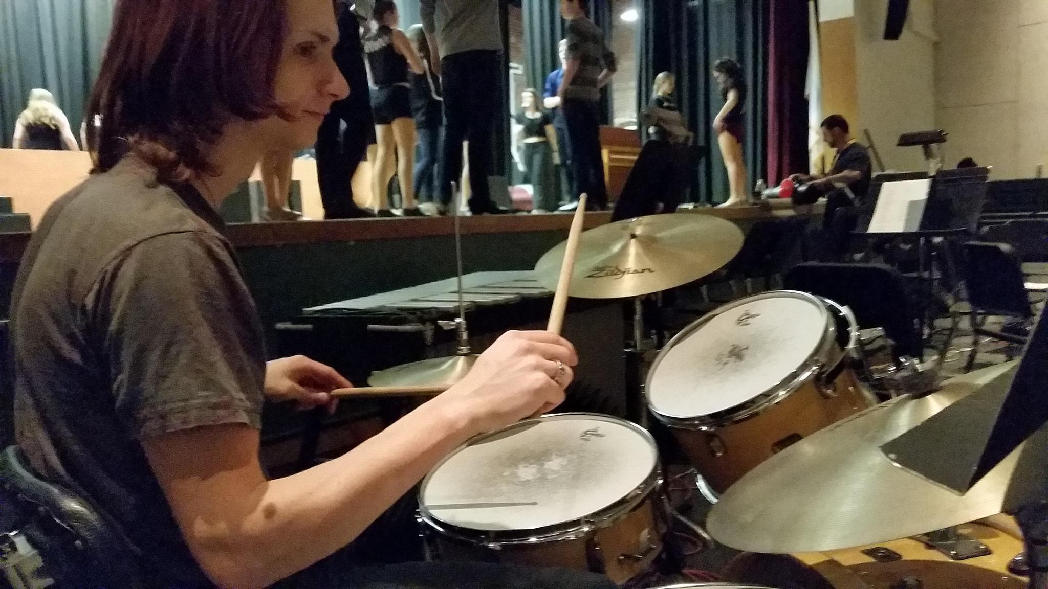 Samuel Faucher practicing the drums prior to the start of a run through.