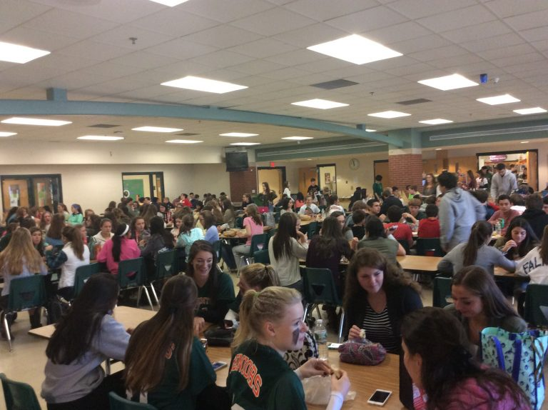 The cafeteria bustles with students during the lunch period.