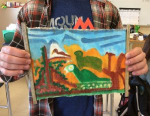 Joe Lanen shows his souvenir painting that he brought back from the Belize trip in Spanish class. Photo by Josh Normandeau.
