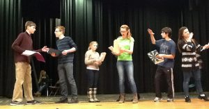 "Evelyn Oliver (center), playing Alice Little, and other cast members (left to right) Erik Fliegauf, Jack McCauliffe, Ashley Olafsen, Henry Vumbaca, and Taylor Forsmo prepare the ""Growing and Shrinking scene"" for the original HHS production of Uncommon Nonsense. The scene is based in a theatrical game in which a new actor enters the stage to create a new scene. As more players are added and new scenes emerge, they eventually exit the stage and the scenes are recycled. Photo by Blair Guild"