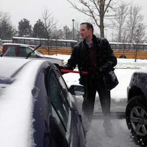 Principal Bishop helps clear staff cars on 2/13/14. (hhspress photo)