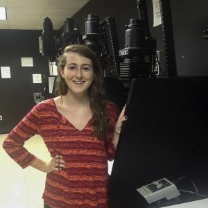 """Club President Avery McKenna is always excited to explain the """"Dark Room""""  Behind her are the englargers used in the process. Photo by: Jill Sullivan"""