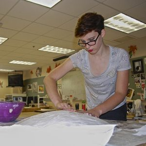 Senior Maddy Boyce works on a shield, a part of her Halloween costume. Photo by Abigail Carbonneau