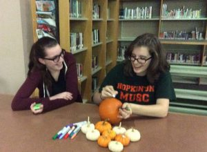 Sophomore, Brianna Maloney and Senior, Sarah Biliter expressing their art skills, by decorating pumpkins at Thursday's Halloween movie event hosted by Book Club. Photo by Sabrina Martin