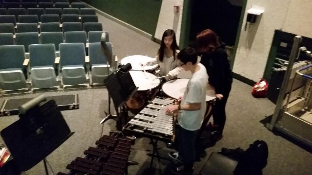 Pit band members Samuel Faucher, Brian Best, and actor Clare Wu looking over the score to the show.