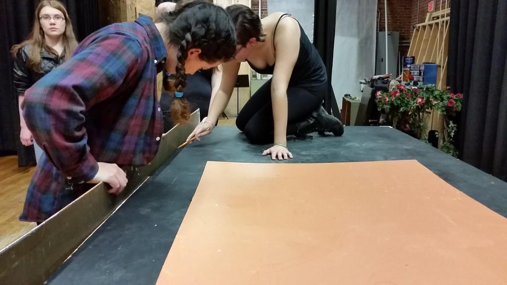 Stage manager McKenzie Simmons and crew member Meg Bradbury preparing to put together set piece.