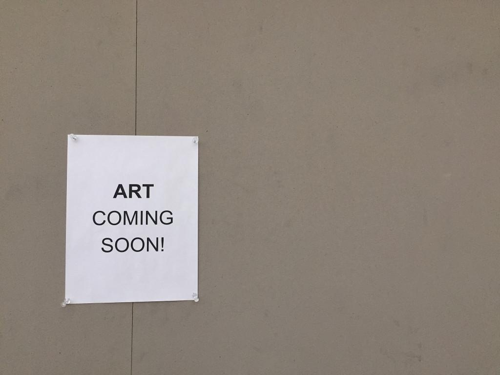 A sign hangs on a bulletin board in the atrium that announces upcoming art projects to be displayed. Photo by Emma Zack.