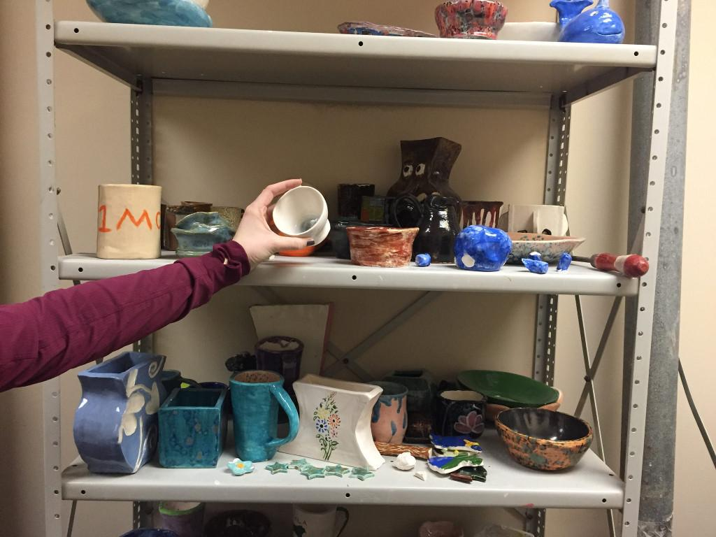 Senior Kayla Patrick picks up her finished project from the shelf and is ready to take it home. Photo by Casey Palmer.