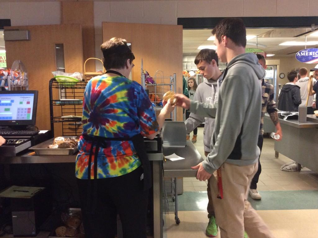 Kathy Bieri sells a cookie to senior Jack Marcou during lunch.
