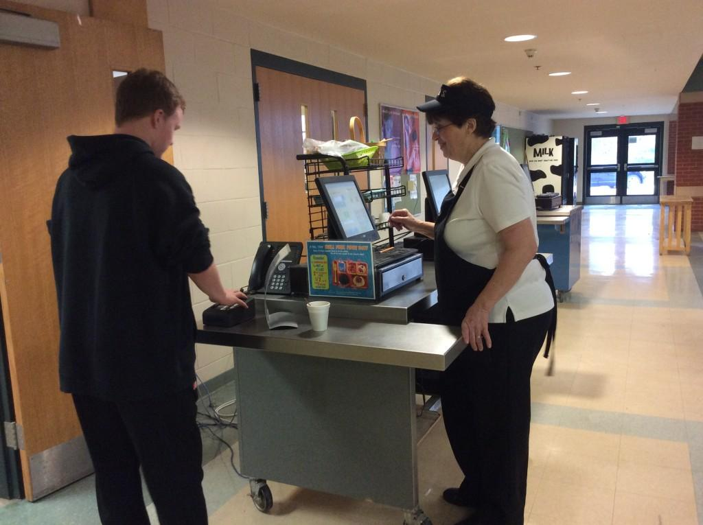 Kathy Bieri helps a student buy hot chocolate, one of many items available for purchase during the breakfast period.