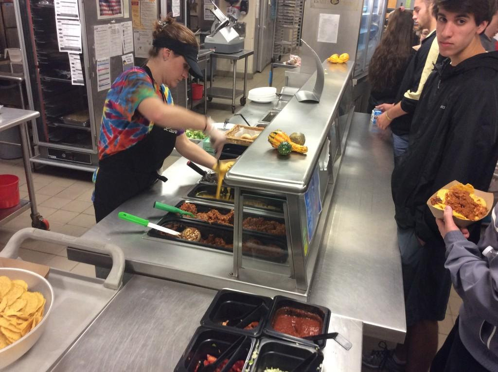 Laura Chatten scoops melted cheese over nachos as the lunch rush enters the cafeteria.