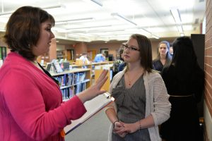 A science fair judge speaks with sophomore Freya Proudman about her project at the 2016 HHS Science Fair, held Mar. 1 in the library. Photo courtesy of Fred Haas.