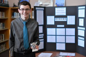 "Junior Brian Best proudly stands beside his third-place winning project, ""Music Math: Does Music Follow a Zipfian Distribution?"" Photo courtesy of Fred Haas."