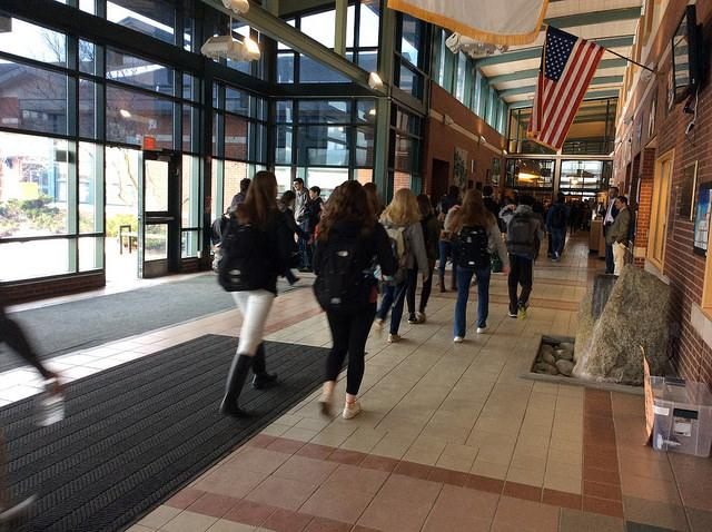 Students strolling into the high school after arriving by school bus or car. Photo by Sarah Fromer.
