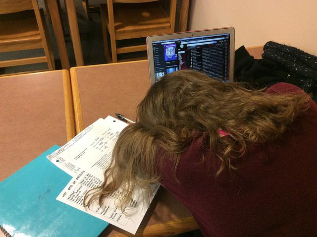 A senior asleep in front of her homework during first period study in the library. Photo by Sarah Fromer.